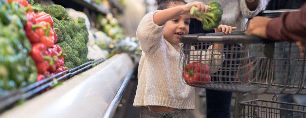 A pre-school age girl helps her parents pick out veggies in the produce section at the grocery store. She is putting a head of broccoli in the cart.